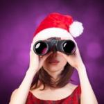 Frau mit Fernglas und Weihnachtsmütze