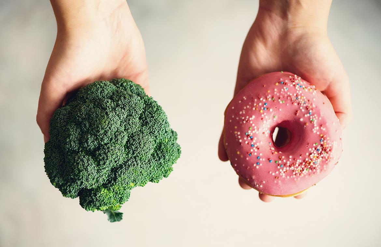 Brokkoli in einer Hand, in der anderen einen Donout