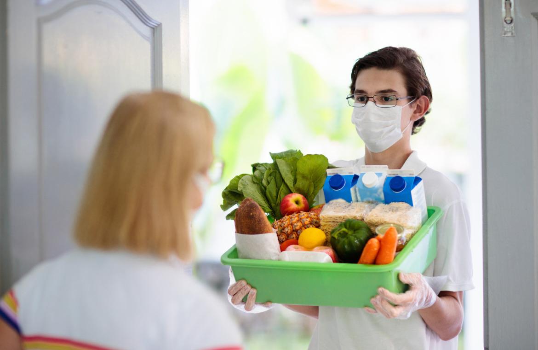 Junger Mann mit Mundschutz und Handschuhen bringt Lebensmittel an die Haustür