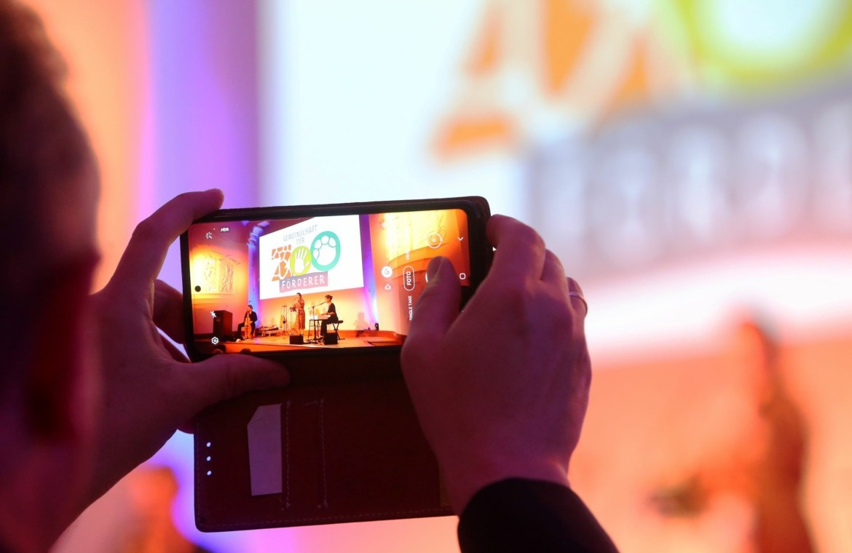 Mann hält Handy und filmt Präsentation